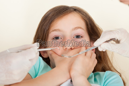 scared girl covering mouth before dental