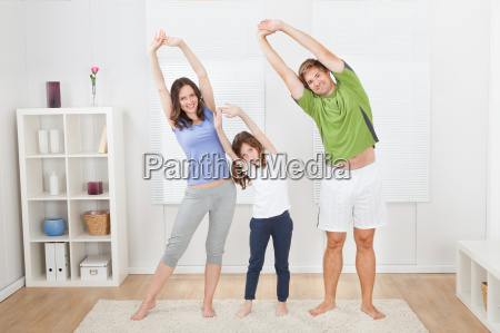 portraet der fit family performing yoga