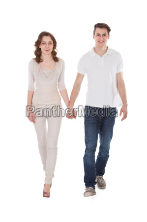 couple in casuals walking over white