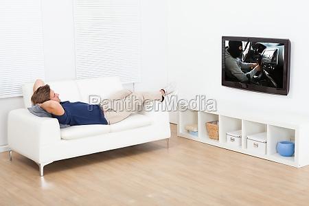 man fernsehen im liegen auf dem