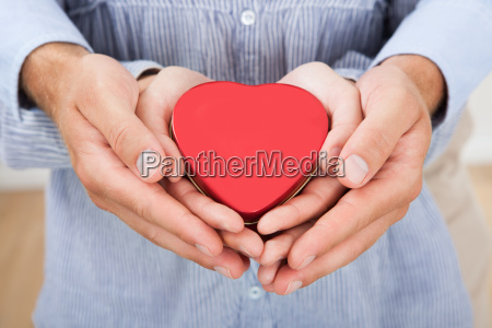 loving couple holding heart at home