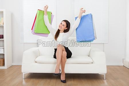 aufgeregte businesswoman holding einkaufsbeutel auf sofa