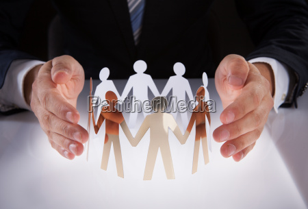 businessmans hands protecting team of paper