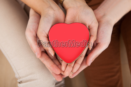 couple holding heart shape in cupped