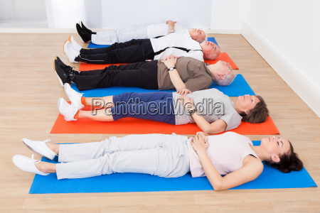 trainer and senior people lying on