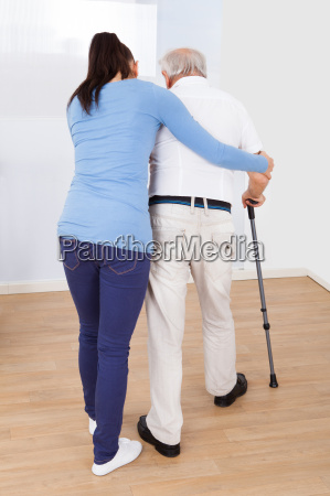 pflegeperson unterstuetzung alter mann mit stock