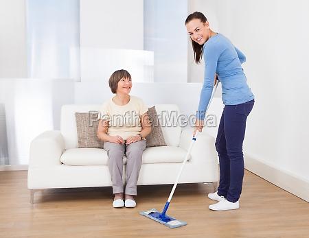 hausmeister reinigung boden waehrend frau sitzt