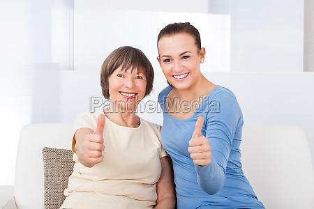 caregiver und aeltere frau zeigt daumen