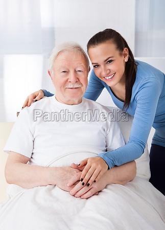 hausmeister mit aelterem mann bei pflegeheim