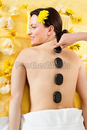 frau erhaelt heisse steintherapie in spa