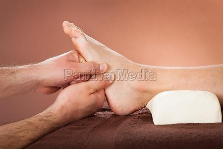 therapeut der fussmassage um kundin im