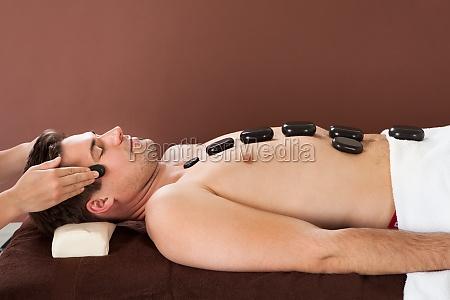 man erhaelt heisse steintherapie in spa