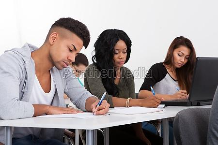 studenten die am schreibtisch schreiben