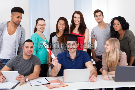 student holding degree mit klassenkameraden ihn