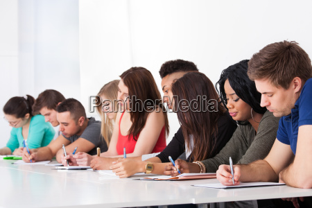 row of college students writing at
