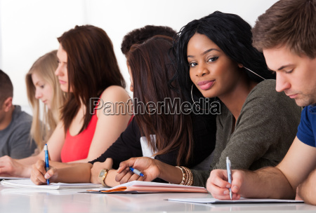 confident student sitting with classmates writing