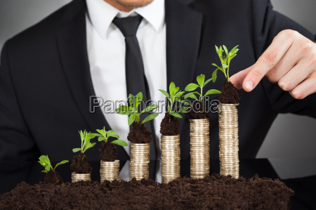 businessman stacking saplings on coins representing