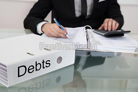 geschaeftsmann kalkuliert schulden am schreibtisch