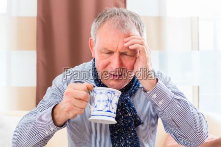 senior trinkt tee und kuriert erkaeltung