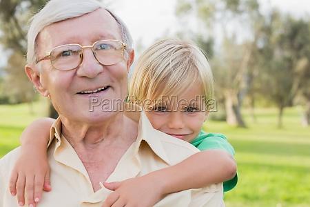 portrait of happy grandfather giving grandson