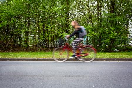 bewegung verwischt weibliche radfahrer auf einer