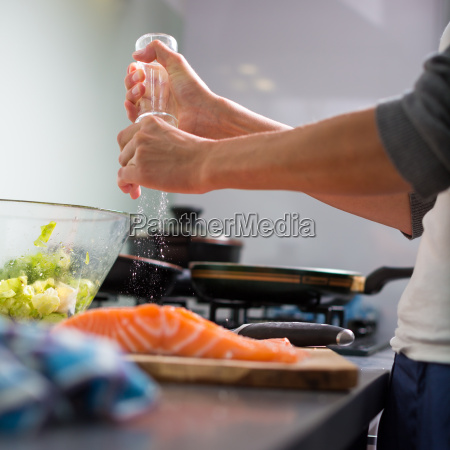 young woman seasoning a salomn filet