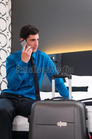mann telefoniert bei anreise im hotel