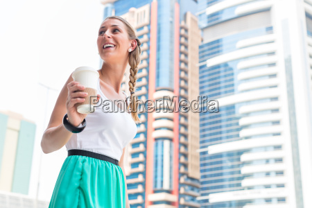 woman enjoys caffee to go in