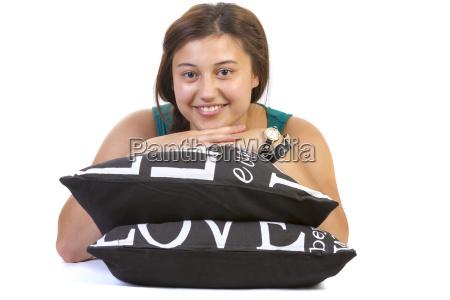 teenage girl lying over pillows
