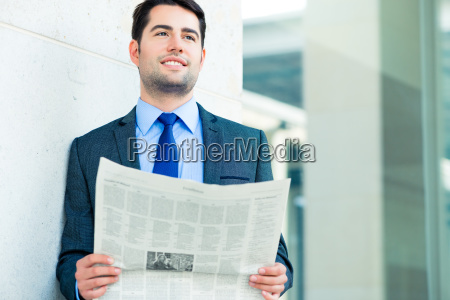manager reading business newspaper