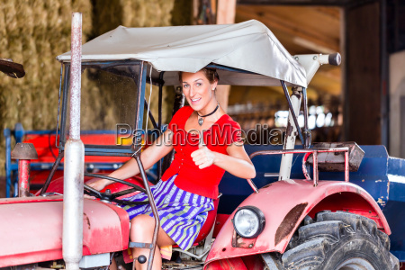 bavarian woman with dirndl driving tractor