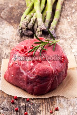 rohes steak mit spargel auf holz