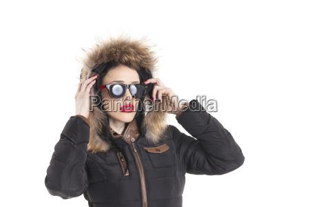 frau mit sonnenbrille in einem wintermantel