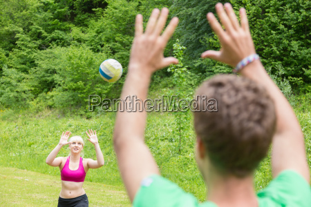 young couple playing volleyball in park