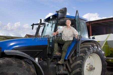 landwirt der sich vom traktor lehnt