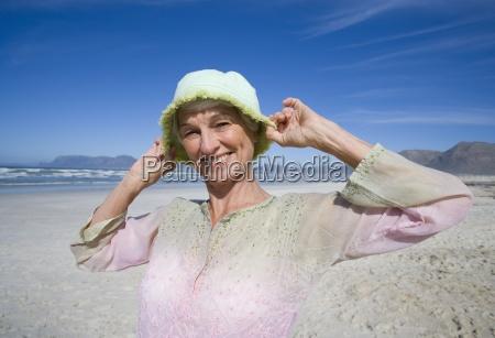 senior woman holding hat on head