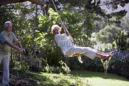 senior woman swinging on garden rope