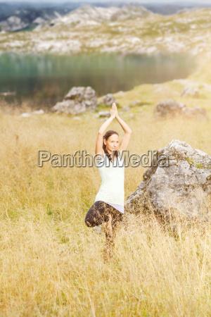 junge frau macht yogauebungen im hohen
