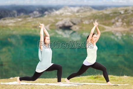 zwei frauen beim yoga vor einem