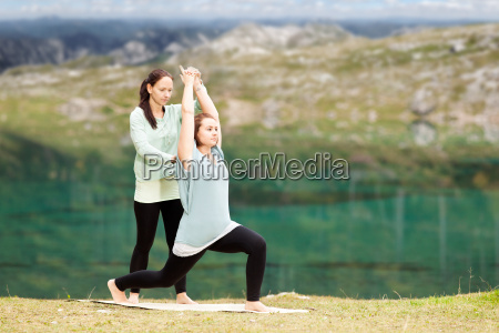 female yoga instructor provides assistance in