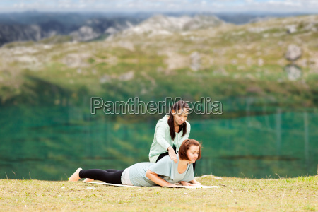 female yoga teacher gives help with