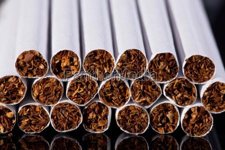 einige duenne zigaretten auf schwarzem hintergrund