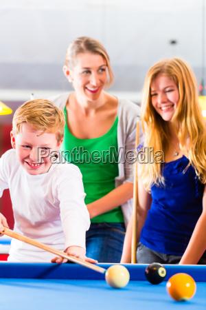 junge spielt pool billard mit familie