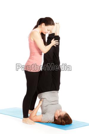 yogalehrerin gibt hilfestellung beim training salamba