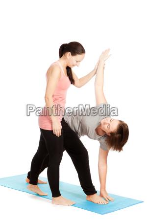 yogalehrerin gibt hilfestellung beim training parivritta