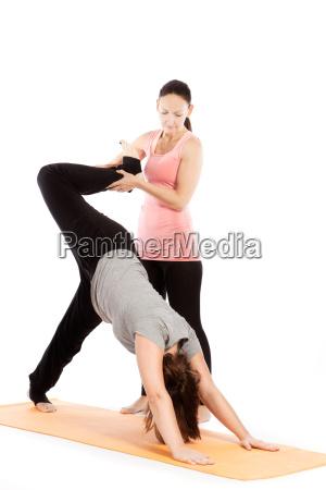 yogalehrerin gibt hilfestellung beim training adho