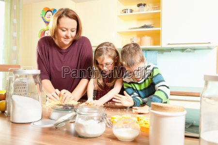 mutter baeckt kekse mit ihren kindern