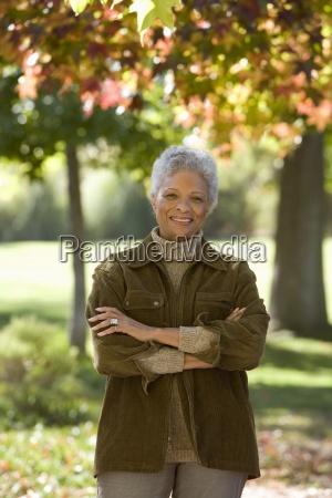 senior woman standing in autumn garden