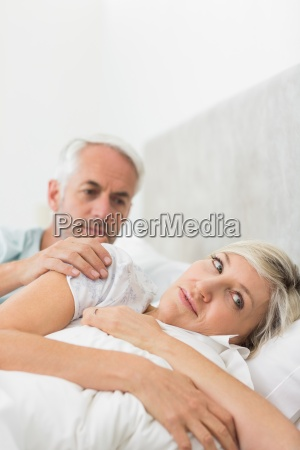woman ignoring mature man in bed