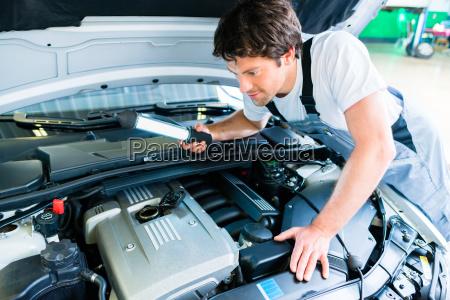 kfz mechaniker arbeitet in autowerkstatt
